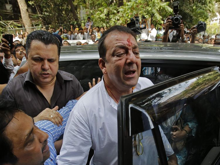 Bollywood actor Sanjay Dutt gets out of a vehicle as he arrives to surrender at a court in Mumbai