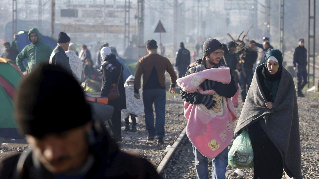 Migrants walk along railway tracks at the Greek-Macedonian border, near the village of Idomeni