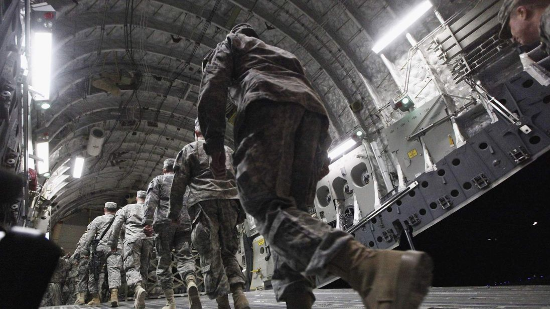 Soldiers from the 3rd Brigade, 1st Cavalry Division board a C-17 transport plane to depart from Iraq at Camp Adder