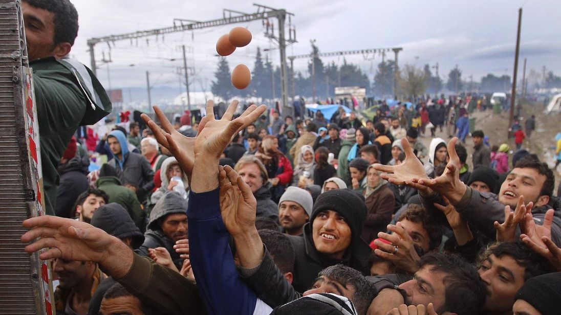 Migrants try to get products from a truck at a makeshift camp on the Greek-Macedonian border near the village of Idomeni