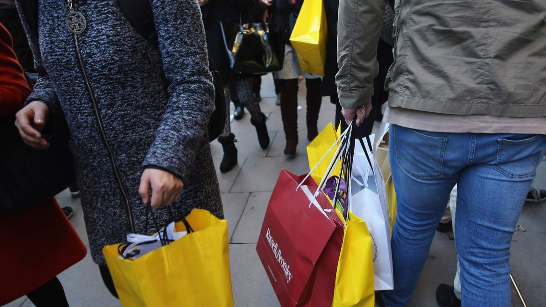 Christmas shoppers carry shopping bags as they crowd Oxford Street on December 13, 2014