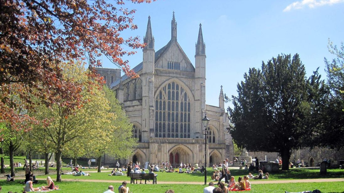 People enjoy the sun at Winchester Cathedral in Winchester, Hampshire