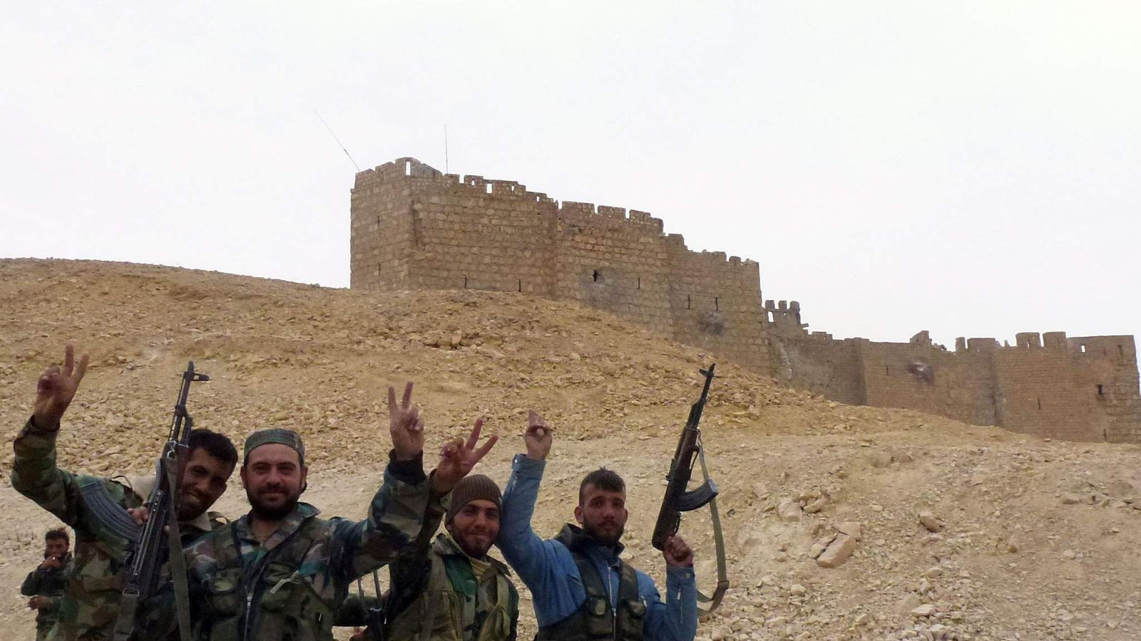 Syrian pro-government forces gesture next to the Palmyra citadel