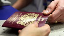 A UK Border Agency officer checks a passport in the North Terminal of Gatwick Airport, Sussex