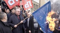 Serbian ultra-nationalist leader Seselj, surrounded by Radical Party supporters, burns NATO flag during a protest in front of the Special Court building in Belgrade