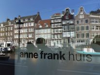 Reflections of tourists and canal houses are seen in the window of the  Anne Frank museum in Amsterdam