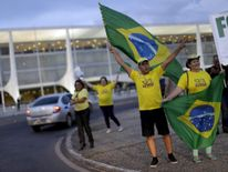 People hold up Brazilian national flags during a protest against former Brazilian President Luiz Inacio Lula da Silva in front of Planalto Palace in Brasilia, Brazil