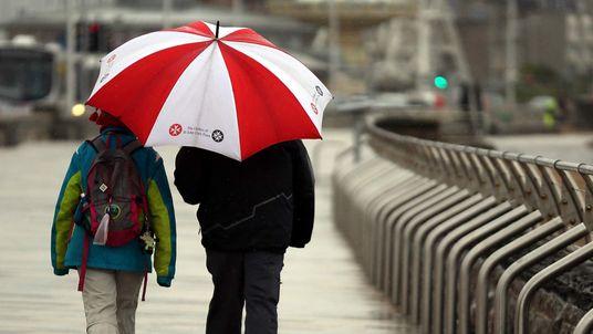 People shelter under an umbrella in Weston-Super-Mare