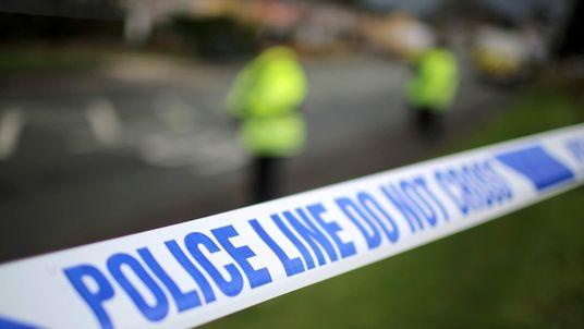 Police tape cordons off a scene