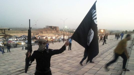 A fighter of the IS holds a flag and a weapon on a street in Mosul