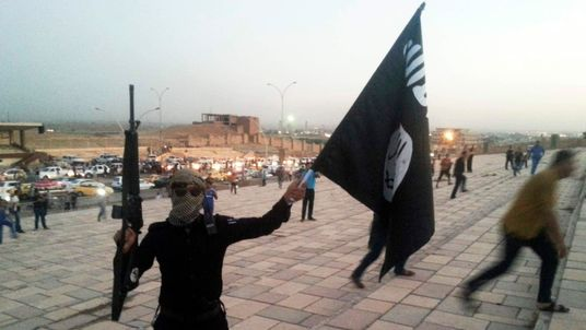 A fighter of the ISIL/ISIS holds a flag and a weapon on a street in Mosul, Iraq