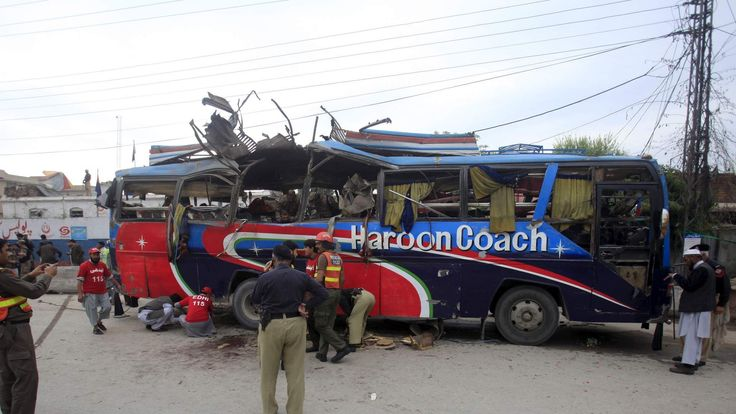 Policemen and rescue officials walk near a bus damaged in a bomb blast in Peshawar