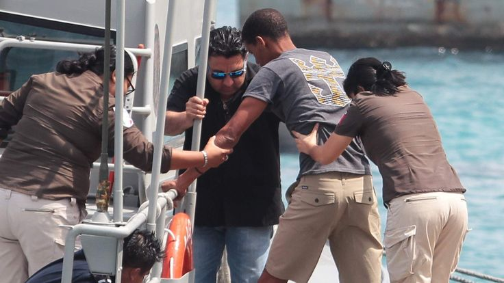A Cuban migrant is being helped by Mexican immigration officers, after he and fellow Cuban migrants were picked up by a cruise ship off the Florida coast, in Cozumel
