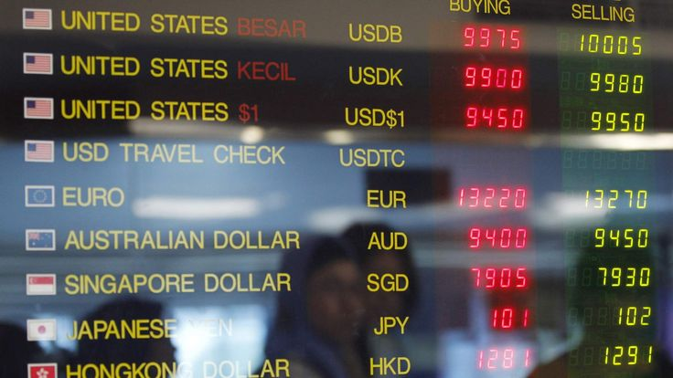 A woman is reflected in an electronic board as she looks at exchange rates of foreign currencies against the Indonesian rupiah at a money changer in Jakarta