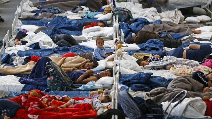 Migrants rest on beds at an improvised temporary shelter in a sports hall in Hanau