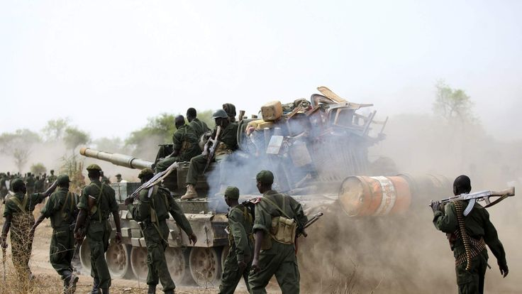South Sudanese soldiers walk alongside a tank as they withdraw from the town of Jau