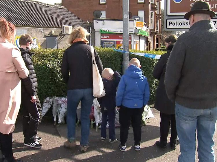 People lay flowers close to the scene where a Glasgow shopkeeper was killed.
