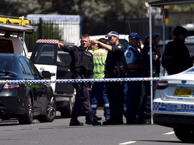 Police and emergency services personnel can be seen behind a road block at the scene of a shooting in the western Sydney suburb of Ingleburn