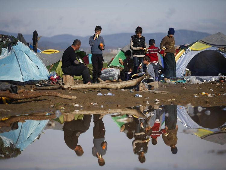 Migrants rest near their tents at a makeshift camp on the Greek-Macedonian border, near the village of Idomeni