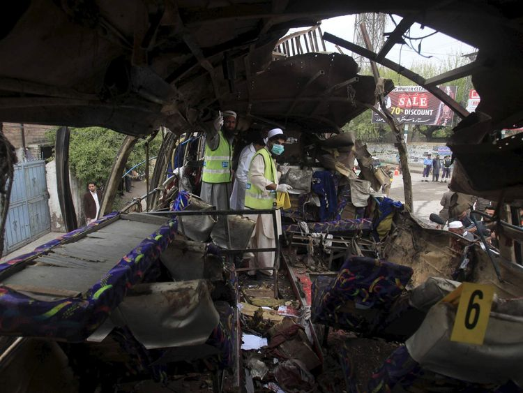Police and rescue personnel search a bus damaged in a bomb blast in Peshawar