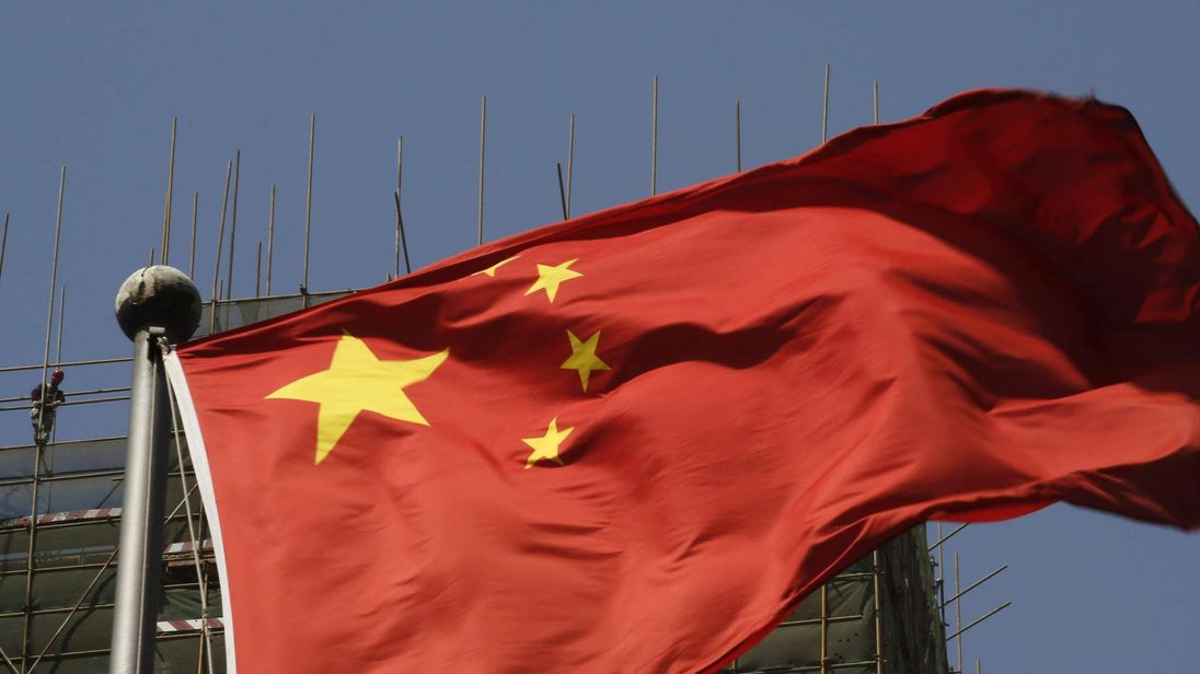 Labourers working at a construction site are pictured behind a Chinese flag in Beijing