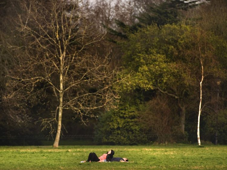 A couple sunbathe in Ruskin Park, London