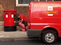 A postman empties a postbox