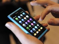 A staff member displays a Nokia N9 smartphone at a news conference in Espoo