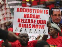 A man holds a placard calling for the release of secondary school girls abducted in the remote village of Chibok, during a protest along a road in Lagos