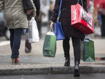 People carry bags outside a shopping mall on the last day of Christmas shopping in Berlin