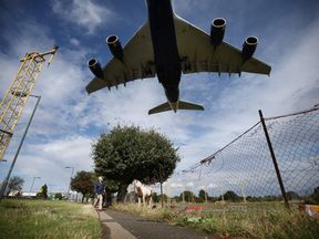 Plane lands at Heathrow airport as debate over third runway continues