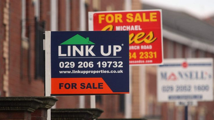 Estate agents signs are displayed outside houses for sale