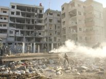 Residents stand near damaged buildings in Daraya.