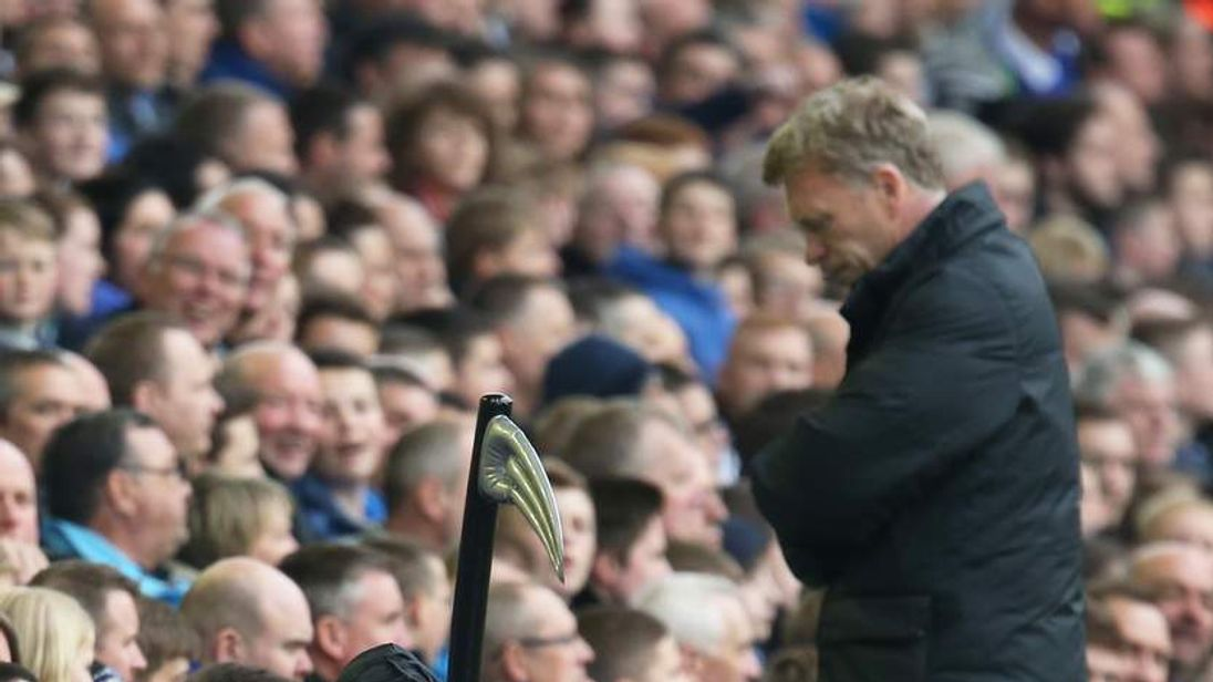 Manchester United manager David Moyes on touchline as a fan dressed as the Grim Reaper watches from the stands.