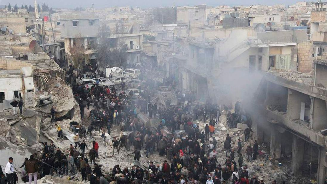 People gather at a site hit by what activists said was missiles fired by a Syrian Air Force fighter jet from forces loyal to Syria's President Bashar al-Assad, at the souk of Azaz