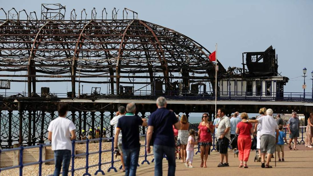 Members of the public walk past Eastbourne Pier.