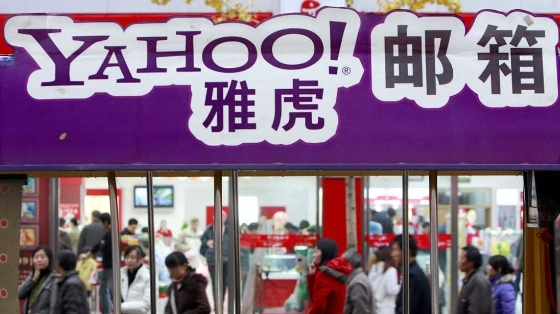 Pedestrians walk past a billboard of Yahoo! in Beijing