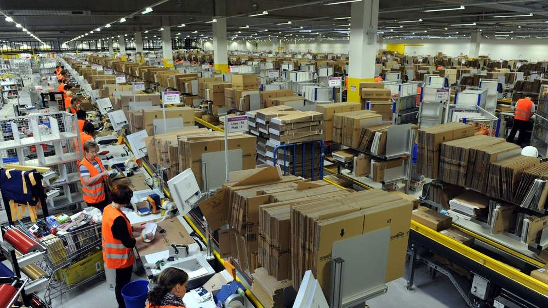 Employees pack parcels at the logistics centre of Amazon in Bad Hersfeld, central Germany