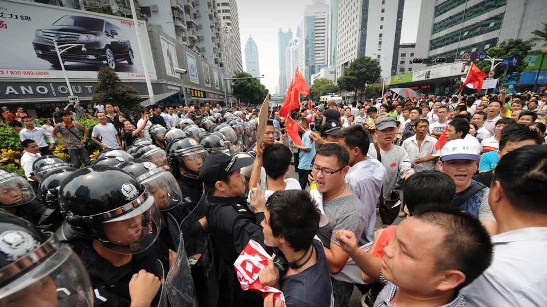 Anti-Japan protesters try to break through a line of riot police during a protest over the Diaoyu islands issue, known as the Senkaku islands in Japan, in the southern Chinese city of Shenzhen on September 18, 2012.