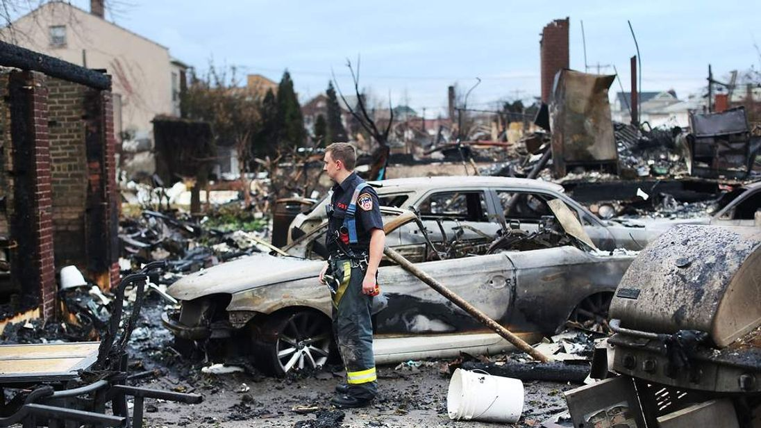 A firefighter stands among the remains of homes burned down in the Rockaway neighborhood during Hurricane Sandy