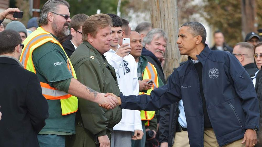 US President Barack Obama greets workers as he visits Cedar Grove Avenue on Staten Island