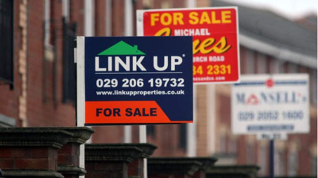 Estate agents signs are displayed outside houses for sale in Cardiff, Wales.