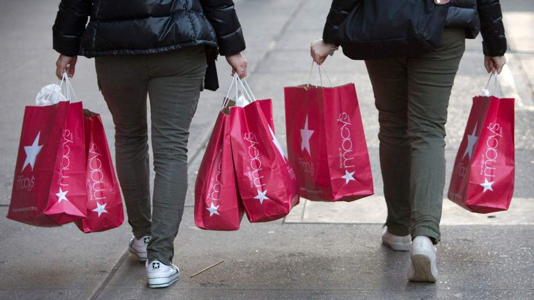 Women carry Macy's bags down 34th Street in New York