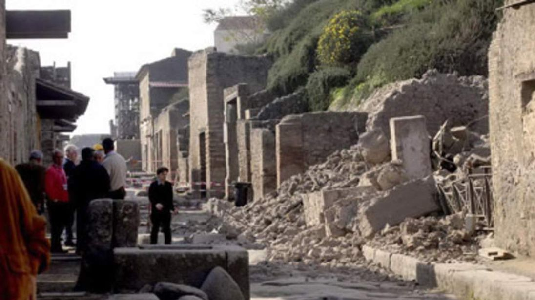 People stand by rubble in the ancient Roman city of Pompeii, Italy.
