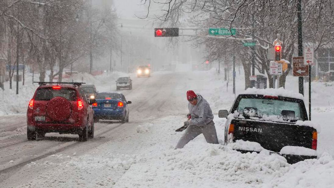 A driver battles to clear snow from around his car in Madison, Wisconsin