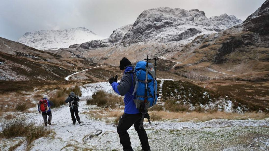 Three people set off for a walk in Glen Coe