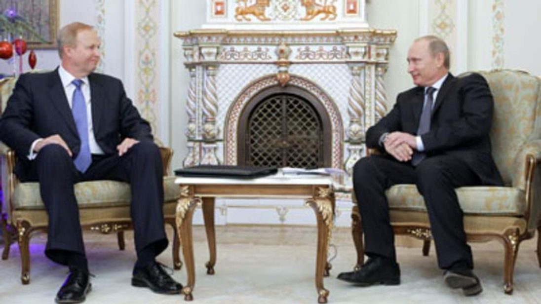 Russian Prime Minister Vladimir Putin (R) speaks with BP chief executive Bob Dudley (L)