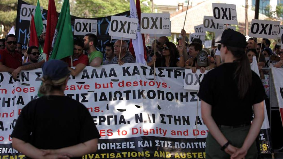 "Cypriot left-wing supporters hold banners reading in Greek: ""No"""