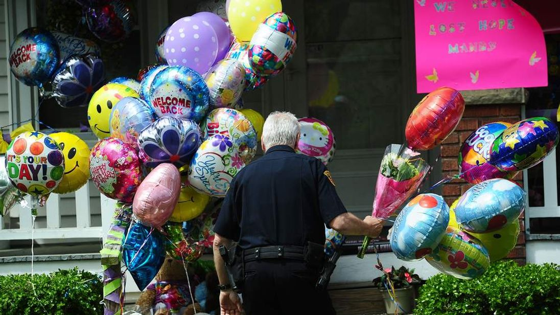 A policeman carries balloons brought by well-wishers before Amanda Berry arrived at her sister's house