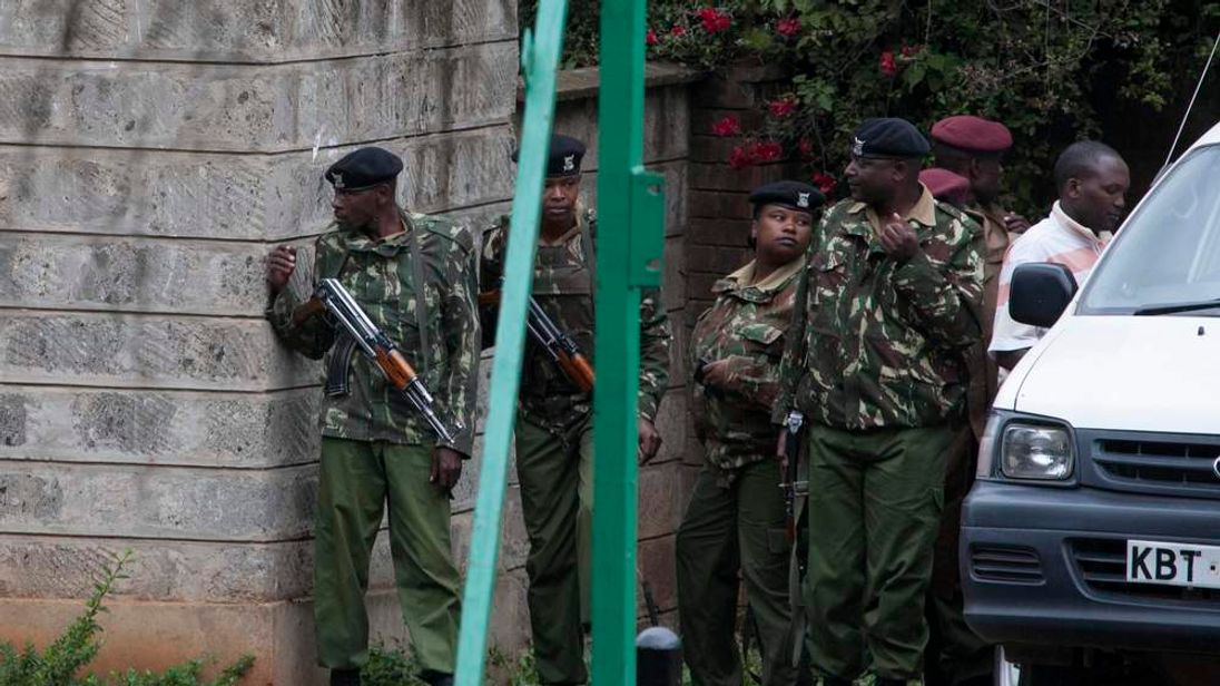 Security officers take cover as they wait for developments, near Westgate Shopping Centre in Nairobi